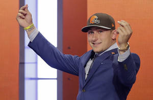 Photo - Texas A&M quarterback Johnny Manziel reacts after being selected by the Cleveland Browns as the 22nd pick in the first round of the 2014 NFL Draft, Thursday, May 8, 2014, in New York. (AP Photo/Frank Franklin II)