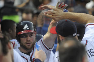 Photo - Atlanta Braves' Brian McCann, left, is congratulated in the dugout after his three-run home run during the third inning of a baseball game against the Cleveland Indians, Thursday, Aug. 29, 2013, in Atlanta. (AP Photo/John Amis)