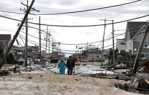 Photo - Robert Bryce, right, walkswith his wife, Marcia Bryce, through destruction from superstorm Sandy on Route 35 in Seaside Heights, N.J., Wednesday, Oct. 31, 2012. Sandy, the storm that made landfall Monday, caused multiple fatalities, halted mass transit and cut power to more than 6 million homes and businesses. (AP Photo/Julio Cortez) ORG XMIT: NJJC109