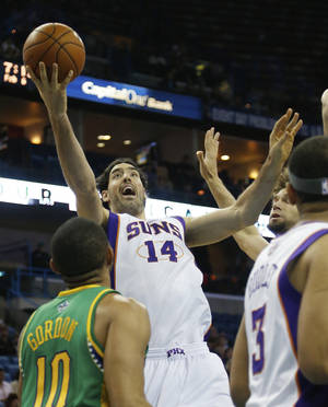 photo - Phoenix Suns power forward Luis Scola (14) drives to the basket as New Orleans Hornets shooting guard Eric Gordon (10) looks on in the first half of an NBA basketball game in New Orleans, Wednesday, Feb. 6, 2013. (AP Photo/Bill Haber)