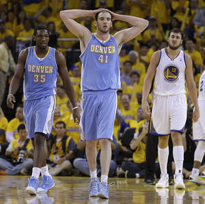 Photo - Denver Nuggets center Kosta Koufos (41) and Kenneth Faried (35) walk off the court during the second half of Game 6 in a first-round NBA basketball playoff series against the Golden State Warriors on Thursday, May 2, 2013, in Oakland, Calif. At right is Warriors' Andrew Bogut.  (AP Photo/Ben Margot)