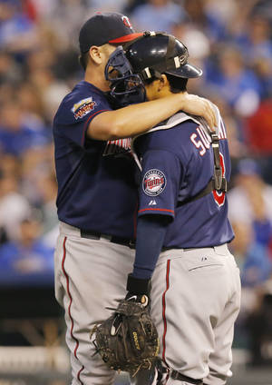 Photo - Minnesota Twins starting pitcher Ricky Nolasco, left, talks with catcher Kurt Suzuki, right, after giving up a run in the third inning of a baseball game against the Kansas City Royals at Kauffman Stadium in Kansas City, Mo., Friday, April 18, 2014. (AP Photo/Orlin Wagner)