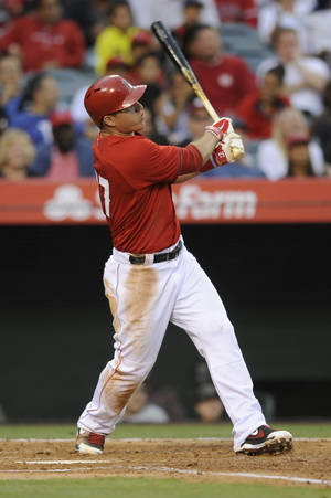 Photo - Los Angeles Angels center fielder Mike Trout follows through on a solo home run during the second inning of an exhibition baseball game against the Los Angeles Dodgers in Anaheim, Calif., Saturday, March 29, 2014. (AP Photo/Kelvin Kuo)