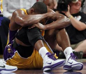 Photo - Los Angeles Lakers' Andrew Bynum holds his knee on the floor after being hurt during the first half of a NBA basketball game against the San Antonio Spurs in Los Angeles, Tuesday, April 12, 2011. Bynum hyperextended his right knee. (AP Photo/Chris Carlson) <strong>Chris Carlson</strong>
