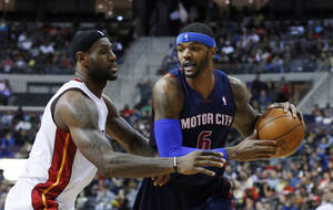 Photo - Miami Heat small forward LeBron James, left,  defends Detroit Pistons small forward Josh Smith (6) in the second quarter of an NBA basketball game in Auburn Hills, Mich., Sunday, Dec. 8, 2013.  (AP Photo/Paul Sancya)