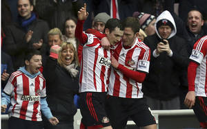 Photo - Sunderland's Adam Johnson, left, celebrates his goal with a teammate during their English Premier League soccer match against Southampton at the Stadium of Light, Sunderland, England, Saturday, Jan. 18, 2014. (AP Photo/Scott Heppell)