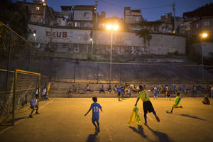 Photo - In this Monday, June 2, 2014 photo, children attend a soccer school class on a court in the Mangueira slum of Rio de Janeiro, Brazil. The aspiring soccer stars of Rio de Janeiro's historic Mangueira slum don't have far to look for inspiration. The slum sits on a hill overlooking Brazil's temple to soccer, the fabled Maracana stadium, where legends from Pele to Neymar have played. (AP Photo/Leo Correa)