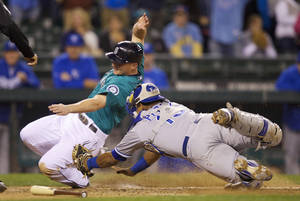 Photo - Kansas City Royals catcher Salvador Perez tags out Seattle Mariners base runner Kyle Seager at home plate when Seager tried to score on a sacrifice fly during the tenth inning of a baseball game, Monday, Sept. 23, 2013, in Seattle. (AP Photo/Stephen Brashear)