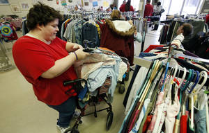 Photo - Lisa Eubanks prices clothes at ReRun Junction, a Norman thrift store run by developmentally disabled adults.  PHOTO BY STEVE SISNEY, THE OKLAHOMAN