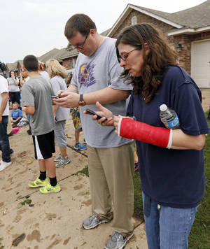 David Wheeler and Karen Wheeler check text messages near SW 156th and Vicki while trying to locate David Wheeler's son and Karen Wheeler's nephew, Gabriel Wheeler, 9, after a tornado struck south Oklahoma City and Moore, Okla., Monday, May 20, 2013. Gabriel Wheeler is a student at Briarwood Elementary, which was destroyed by the tornado. Photo by Nate Billings, The Oklahoman