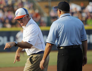 Photo - Florida head coach Tim Walton argues with umpire Kevin Davis in the first inning during game 1 of the Women's College World Series championship softball final between the University of Florida and Arizona State University at ASA Hall of Fame Stadium in Oklahoma City, Monday, June 6, 2011. Photo by Nate Billings, The Oklahoman