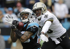 Photo - FILE - In this Dec. 22, 2013, file photo, Carolina Panthers' Steve Smith, left, catches a pass as New Orleans Saints' Keenan Lewis, right, defends in the first half of an NFL football game in Charlotte, N.C. The Panthers released their all-time leading receiver on Thursday, March 13, 2014, after 13 seasons.  (AP Photo/Chuck Burton, File)