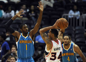Photo -   New Orleans Hornets' Hakim Warrick (1) guards Atlanta Hawks' Devin Harris (34) as Hornets' Xavier Henry (4) looks on in the half of a preseason NBA basketball game in Atlanta, Thursday, Oct. 18, 2012. (AP Photo/David Tulis)