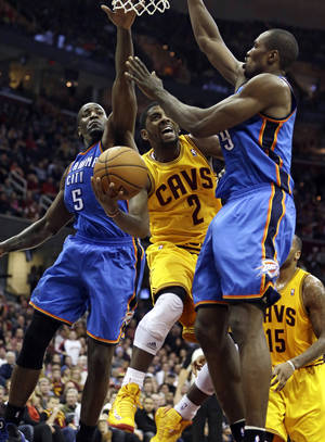 photo - Cleveland Cavaliers' Kyrie Irving (2) shoots to the basket against Oklahoma City Thunder's Kendrick Perkins (5) and Serge Ibaka (9), from the Republic of Congo, during the fourth quarter of an NBA basketball game on Saturday, Feb. 2, 2013, in Cleveland. The Cavaliers won 115-110. (AP Photo/Tony Dejak) ORG XMIT: OHTD109