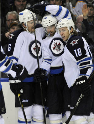 photo - Winnipeg Jets&#039; defenseman Ron Hainsey (6), left winger Andrew Ladd (16) and center Brian Little (18) celebrate a goal by Ladd during the second period of an NHL hockey game against the Buffalo Sabres in Buffalo, N.Y., Tuesday, Feb. 19, 2013. (AP Photo/Gary Wiepert)