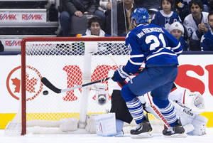 Photo - Toronto Maple Leafs Forward James van Riemsdyk (21) scores past New Jersey Devils goalie Cory Schneider to defeat the devils in a shoot out during a NHL hockey game in Toronto on Sunday, Jan. 12, 2014.  (AP Photo/The Canadian Press, Nathan Denette)