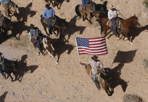 In this April 12, 2014, file photo, the Bundy family and their supporters fly the American flag as their cattle is released by the Bureau of Land Management back onto public land outside of Bunkerville, Nev.  The federal Bureau of Land Management says six cattle died in the roundup of animals it says rancher Cliven Bundy allowed to graze illegally on public land outside his southern Nevada property. The BLM said Tuesday, April 22, 2014, that two of four animals that were euthanized bore Bundy brands. (AP Photo/Las Vegas Review-Journal, Jason Bean, File) LOCAL TV OUT; LOCAL INTERNET OUT; LAS VEGAS SUN OUT