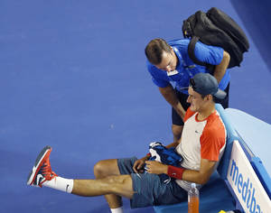 Photo - Bernard Tomic of Australia talks to medical staff during his first round match against Rafael Nadal of Spain at the Australian Open tennis championship in Melbourne, Australia, Tuesday, Jan. 14, 2014.(AP Photo/Eugene Hoshiko)