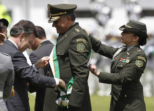 Photo -   Former National Police Chief Gen. Oscar Naranjo, center, is decorated by President Juan Manuel Santos during the swearing-in ceremony of Naranjo's replacement in Bogota, Colombia, Tuesday, June 12, 2012. Gen. Jose Roberto Leon Riano replaced Naranjo. (AP Photo/Fernando Vergara)