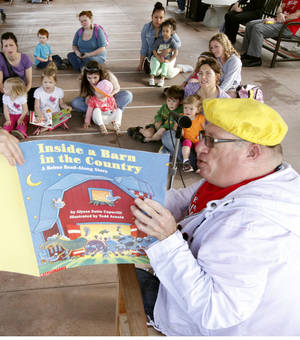 Photo - Above: John Divelbiss, an employee of Oklahoma City Public Schools, reads to children Tuesday during Read Across Oklahoma at the Oklahoma City Zoo.