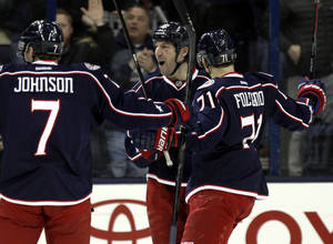 Photo - Columbus Blue Jackets' R.J. Umberger, center, celebrates his goal against the Los Angeles Kings with teammates Jack Johnson, left, and Nick Foligno in the first period of an NHL hockey game in Columbus, Ohio, Tuesday, Jan. 21, 2014. The Blue Jackets won 5-3. (AP Photo/Paul Vernon)