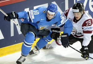 Photo - FILE - In this Tuesday, May 14, 2013 file photo, Finland's Juhamatti Aaltonen, left, vies for the puck with Latvia's Ralfs Freibergs during the 2013 Ice Hockey IIHF World Championships Group B preliminary round match in Helsinki. Two months after the closing ceremony, the Sochi Olympics broke a Winter Games record Friday, April 25, 2014 when a Latvian hockey player became the eighth athlete disqualified for a positive doping test. Ralfs Freibergs was retroactively kicked out of the games by the IOC after being found guilty of a steroid offense, the third hockey player and second from Latvia caught for doping in Sochi. (AP Photo/Lehtikuva, Jussi Nukari, File) FINLAND OUT