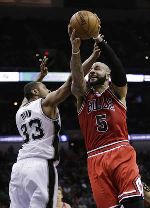 Photo - Chicago Bulls' Carlos Boozer (5) shoots as San Antonio Spurs' Boris Diaw (33) defends during the second half of an NBA basketball game, Wednesday, Jan. 29, 2014, in San Antonio. (AP Photo/Eric Gay)