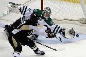 Photo - Pittsburgh Penguins' Sidney Crosby (87) backhands a shot past Dallas Stars goalie Kari Lehtonen (32) for a goal during the first period of an NHL hockey game in Pittsburgh, Tuesday, March 18, 2014. (AP Photo/Gene Puskar)