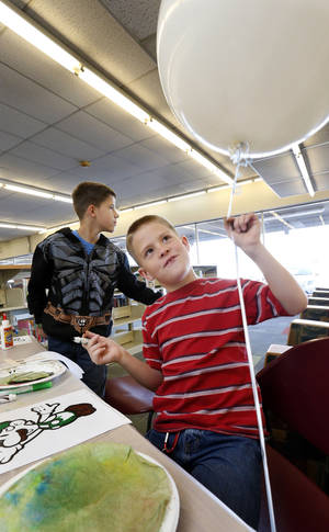 Photo - Joshua Grissom, 9, right, and brother Daniel, 10, attend the library's reopening.