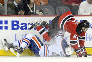 Photo - New Jersey Devils' Andy Greene (6) checks Edmonton Oilers' Taylor Hall to the ice during the first period of an NHL hockey game on Friday, Feb. 7, 2014, in Newark, N.J. (AP Photo/Bill Kostroun)