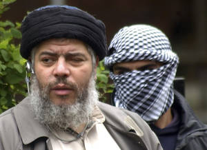 Photo -   FILE - This Friday, April 30, 2004 file photo shows Muslim cleric Abu Hamza al-Masri, as he arrives with a masked bodyguard, right, to conduct Friday prayers in the street outside the closed Finsbury Park Mosque in London. Al-Masri pleaded not guilty Tuesday, Oct, 9, 2012 to charges that he conspired with Seattle men to set up a terrorist training camp in Oregon. Al-Masri entered the plea shortly before U.S. District Judge Katherine B. Forrest set an Aug. 26 trial date for al-Masri. (AP Photo/Max Nash, File)