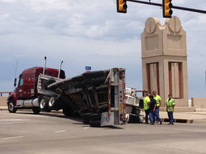 Photo -  A tractor-trailer lost its payload Tuesday afternoon on a Pennsylvania Avenue bridge north of Interstate 40. Oklahoma City police received the call about noon and sent a wrecker to assist with the cleanup. It is unclear how the payload tipped over and onto the road, police said. Photo by Steve Gooch, The Oklahoman   <strong>   -   </strong>