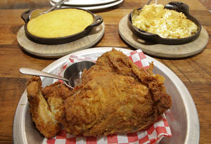 Photo - This photo taken May 17, 2014 shows fried chicken and side dishes, spoonbread, rear left, and mac & cheese, at The Eagle restaurant in the Over-the-Rhine neighborhood of Cincinnati, a picturesque neighborhood on the edge of downtown that locals simply call OTR. (AP Photo/Al Behrman)