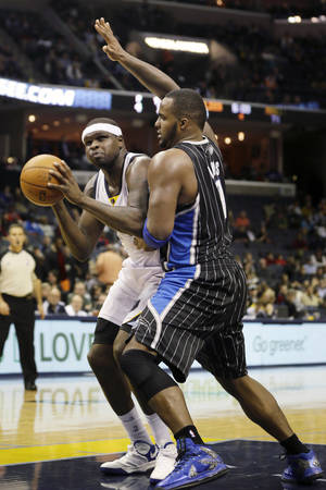 Photo - Memphis Grizzlies' Zach Randolph, left, is defended by Orlando Magic's Glen Davis in the second half of an NBA basketball game in Memphis, Tenn., Monday, Dec. 9, 2013. Randolph made 19 points as the Grizzlies won 94-85. (AP Photo/Danny Johnston)