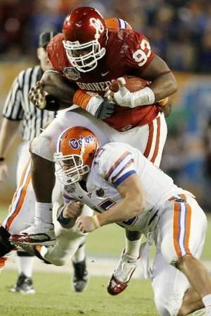 Photo - OU's  Gerald  McCoy tries to get by Florida's Tim Tebow after an interception during the first half of the BCS National Championship college football game between the University of Oklahoma Sooners (OU) and the University of Florida Gators (UF) on Thursday, Jan. 8, 2009, at Dolphin Stadium in Miami Gardens, Fla. By Bryan Terry