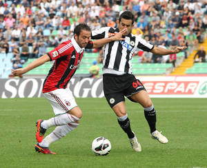 Photo -   AC Milan's Giampaolo Pazzini, left, and Udinese's Giampiero Pinzi, challenge for the ball during a Serie A soccer match, at the Friuli Stadium in Udine, Italy, Sunday, Sept. 23, 2012. (AP Photo/Paolo Giovannini)