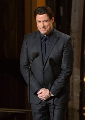 Photo - Presenter John Travolta speaks during the Oscars at the Dolby Theatre on Sunday, March 2, 2014, in Los Angeles.  (Photo by John Shearer/Invision/AP)
