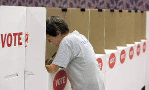 Photo - Martha King of Oklahoma City casts an absentee vote at the Oklahoma County Election Board in Oklahoma City.  By Sarah Phipps