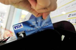 photo - A Chinese man swipes his credit card in Beijing on July 22, 2010. Chinese banks will face rising bad loans in the next few years as economic growth slows and local government investment vehicles struggle to repay their debts, a global rating agency warned. AFP PHOTO/Franko Lee (Photo credit should read Franko Lee/AFP/Getty Images)