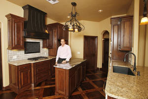 Photo - Kurt Dinnes, president of the Central Oklahoma Home Builders Association and co-owner of Sun Custom Homes, shows the kitchen at 9032 NW 147 Terrace, a home he built for the Parade of Homes, which continues through Sunday. <strong>PAUL B. SOUTHERLAND - THE OKLAHOMAN</strong>