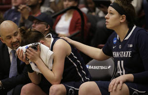 Photo - Penn State guard Maggie Lucas, center, is consoled by a assistant coach Fred Chmiel, left, and guard/forward Jenny DeGraaf (41) while sitting on the bench during the second half of a regional semifinal game against Stanford at the NCAA college basketball tournament in Stanford, Calif., Sunday, March 30, 2014. Stanford won 82-57. (AP Photo/Jeff Chiu)