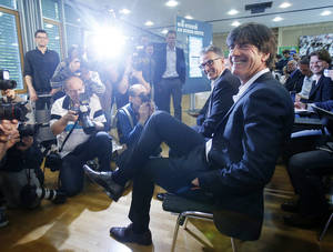 Photo - Joachim Loew, the coach of German national soccer team, smiles as he waits for the beginning of a press conference where he presented his preliminary team for the upcoming World Cup in Brazil in Frankfurt, Germany, Thursday, May 8, 2014. (AP Photo/Michael Probst)