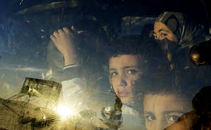 Photo - Syrian children look through their car window as they cross into Lebanon with their families at the border crossing, in Masnaa, eastern Lebanon, Friday, Nov. 30, 2012. (AP Photo/Hassan Ammar)