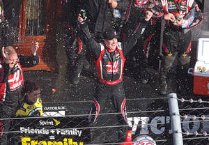 Photo - Driver Kurt Busch celebrates in victory lane after winning a NASCAR Sprint Cup auto race at Martinsville, Speedway in Martinsville, Va., Sunday March 30, 2014. (AP Photo/Steve Shappard)