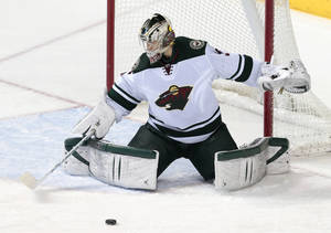 Photo - Minnesota Wild goalie Darcy Kuemper blocks a shot against the Nashville Predators in the third period of an NHL hockey game, Sunday, Jan. 12, 2014, in Nashville, Tenn. Kuemper stopped 23 shots as the Wild won 4-0. (AP Photo/Mark Humphrey)