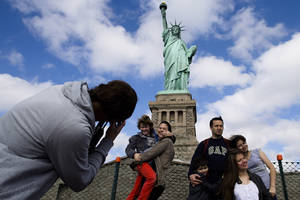 Photo - Tourists pose for photographs in front of the Statue of Liberty in New York Harbor, Sunday, Oct. 13, 2013, in New York. The Statue of Liberty reopened to the public after the state of New York agreed to shoulder the costs of running the site during the partial federal government shutdown. (AP Photo/John Minchillo)