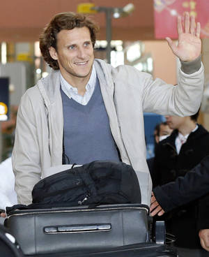 Photo - Uruguay striker Diego Forlan waves to supporters on his arrival at Kansai International Airport in Osaka, western Japan Wednesday, Feb. 12, 2014. Forlan will play for Cerezo Osaka in Japan. (AP Photo/Kyodo News) JAPAN OUT, MANDATORY CREDIT