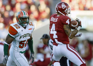 Photo -   Oklahoma wide receiver Kenny Stills catches a pass in front of Florida A&M linebacker Brandon Hepburn (52) in the first quarter of an NCAA college football game in the Gaylord Family Memorial Stadium in Norman, Okla., Saturday, Sept. 8, 2012. Oklahoma won 69-13. (AP Photo/Sue Ogrocki)