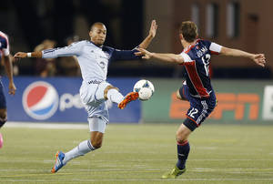 Photo - Sporting Kansas City's Teal Bunbury kicks the ball away from New England Revolution's Andy Dorman (12) in the first half of an MLS Eastern Conference semifinal-round soccer game in Foxborough, Mass., Saturday, Nov. 2, 2013. (AP Photo/Michael Dwyer)
