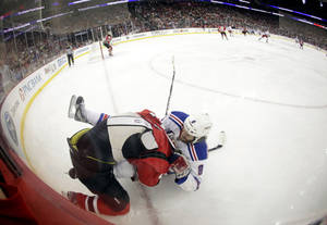 Photo -   In this image made with a fisheye lens, New Jersey Devils defenseman Anton Volchenkov, top, of Russia, and New York Rangers' Brandon Prust wrestle in the corner during the first period of Game 3 of an NHL hockey Stanley Cup Eastern Conference final playoff series Saturday, May 19, 2012, in Newark, N.J. (AP Photo/Julio Cortez)